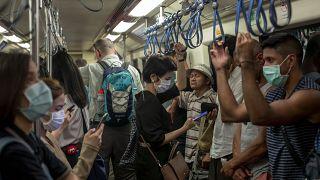 أشخاص يرتدون الأقنعة ويركبون مترو الأنفاق