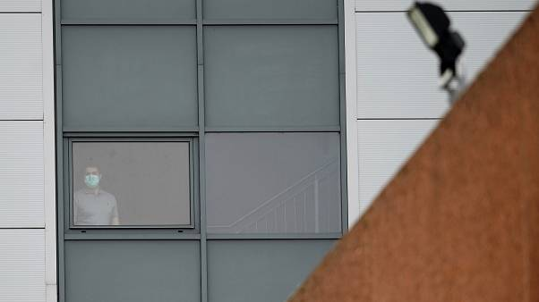 An person wearing a mask stands at a window of a staff accomodation block at Arrowe Park Hospital on the Wirral.
