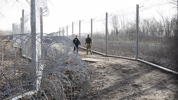 FILE: A Hungarian policeman and a military personnel patrol at the border station between Roszke, Hungary, and Horgos, Serbia, Wednesday, Jan. 29, 2020