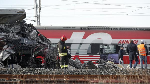 The wreckage of the locomotive of a high-speed train crammed onto another train on adjacent tracks, as the rest of train is seen in the background, after it derailed. Italy.