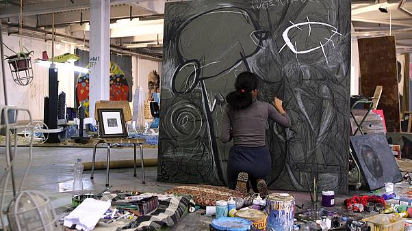 Artist Tara Abdullah paints in her studio, located inside an old tobacco factory