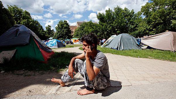 Un migrant originaire du Pakistan parle au téléphone dans le parc en face de la mairie de Sarajevo, en Bosnie, le jeudi 17 mai 2018.
