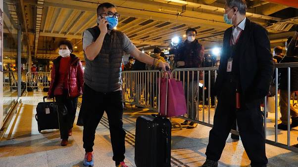 Passengers from the cruise ship World Dream docked at Kai Tak cruise terminal leave the ship after be quarantined for the coronavirus in Hong Kong, Sunday, Feb. 9, 2020