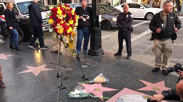 Hollywood Walk of Fame star of actor Kirk Douglas, with wreath of flowers on stand and two bouquets of flowers on ground