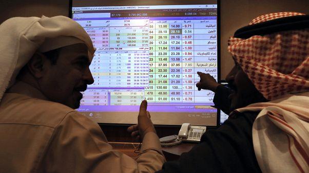 صورة من الأرشيف- يتحدث تجار سعوديون وهم يتابعون شاشة تعرض قيم سوق الأسهم السعودية