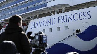 Un periodista con su cámara junto al crucero Diamond Princess, Yokohama, Japón