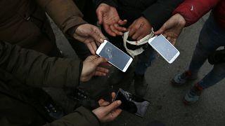 Un gruppo di migranti mostra i telefoni distrutti nel villaggio di Horgos, Serbia, nel gennaio 2020. Siamo vicino al confine ungherese
