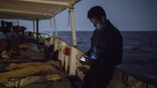 A migrant checks is cellular phone as other sleep on the deck of the Open Arms aid boat, of Proactiva Open Arms Spanish NGO, Sunday, July 1, 2018.