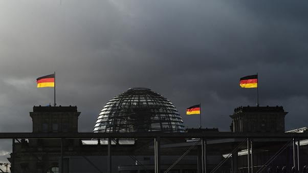 German national flags catch the sun on top of the German parliament building, the Reichstag building in Berlin, Germany, Friday, Nov. 29, 2019.
