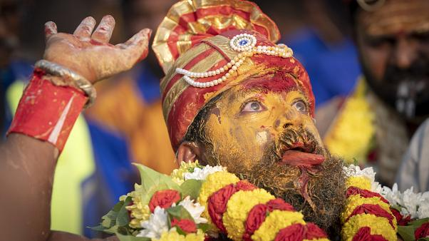 A Tamil Hindu priest has antiseptic powder on his face in a procession during the Thaipusam festival