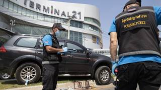 Forensic officers inspect a shooting scene outside the Terminal 21 Korat mall in Nakhon Ratchasima, Thailand, Sunday, Feb. 9, 2020.