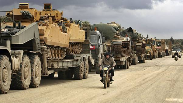 Turkish military convoy drives through the village of Binnish, in Idlib province, Syria, Saturday, Feb. 8, 2020.