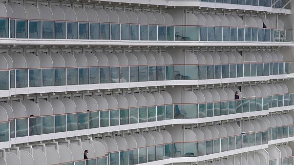 Passenger are seen from the World Dream cruise ship docked at Kai Tak cruise terminal Hong Kong, Wednesday, Feb. 5, 2020.  (AP Photo/Vincent Yu)