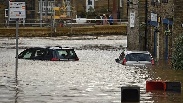 Cars are seen submerged as flood water covers the roads and car parks in Mytholmroyd, northern England.