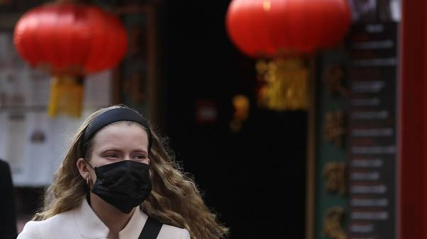 A woman wears a mask as she walks near China Town in London, Friday, Feb. 7, 2020.