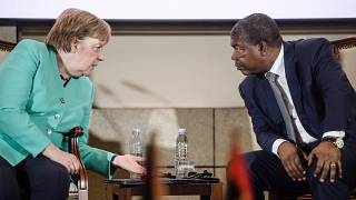 German Chancellor Angela Merkel (L) and Angola's President Joao Lourenco talk during a contract signing ceremony at the German-Angolan economy forum in Luanda