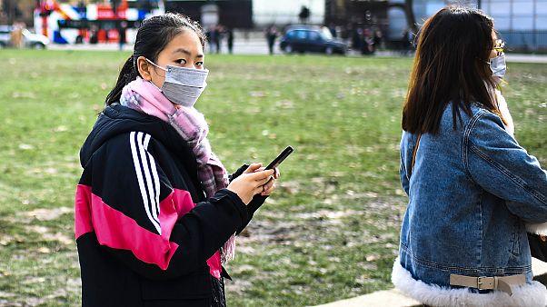 Londra'da koronavirüs salgını nedeniyle maske takan insanlar