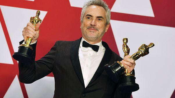 """Alfonso Cuaron posa con los premios al mejor director para """"Roma"""", mejor película en lengua""""Roma"""", y mejor fotografía para """"Roma"""" en febrero de 2019"""