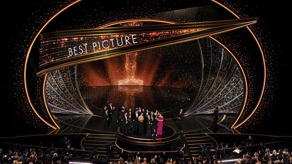 """The cast and crew of """"Parasite"""" accept the award for best picture at the Oscars"""