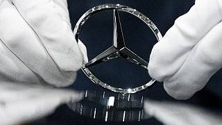 Trabalhador limpa logo da Mercedes Benz numa fábrica da marca
