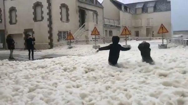 Crianças brincam no meio da espuma deixada pelo mar durante a tempestade
