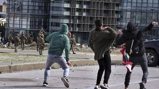 Anti-government protesters throw stones toward Lebanese army soldiers in downtown Beirut, Lebanon, Tuesday, Feb. 11, 2020.