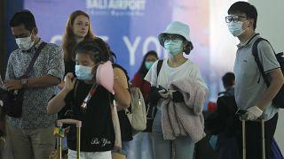 سياح يرتدون أقنعة الوجه في مطار بالي، إندونيسيا  8 فبراير 2020.