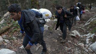 Migrants climb through woods near Bosnia-Croatia border near Bihac, northwestern Bosnia, Sunday, Dec. 8, 2019.