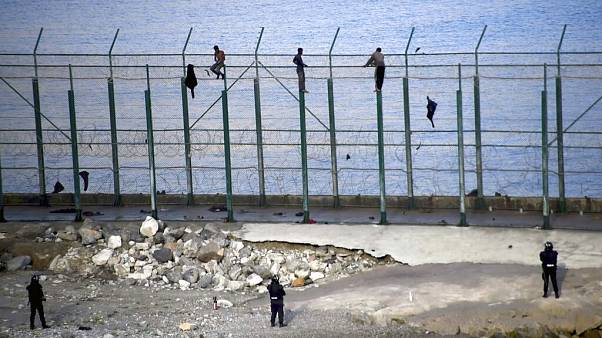 Migrants climb a fence that divides Morocco and Ceuta in this 2019 file photo
