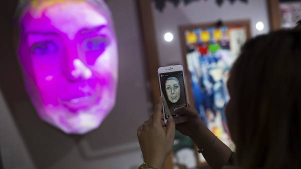 FILE PHOTO - A woman takes a photograph of her own portrait displayed in 3D at the NTT company stand during the Mobile World Congress wireless show, in Barcelona, Spain