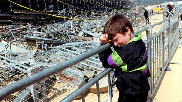 FILE PHOTO: A boy leans on a fence 06 May 1992 in front of the temporary stand at Furiani stadium in Corsica that collapsed 05 May.