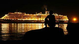 """رجل يرقب السفينة التي تملكها """"هولاند أمريكا لاين""""، وهي راسية في ميناء سيهانوكفيل صباح الجمعة، قبيل هبوط مئات المسافرين منها."""