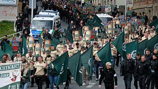 Protestors march with flags during a demonstration of the far-right party 'The third way' in Plauen, Germany, Wednesday, May 1, 2019