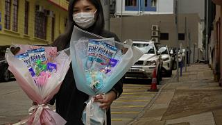 Flower shop owner Iris Leung wears her protective face mask as she delivers flowers with masks to customers on Valentine's Day in Hong Kong, Friday, Feb. 14, 2020.