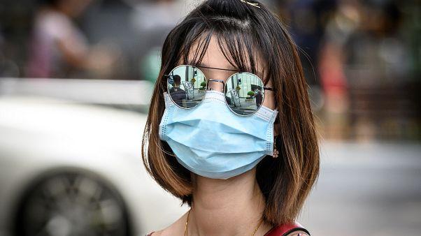 سيدة تضع كمامة على وجهها للوقاية من فيروس كورونا في شوارع بانكوك في تايلاند. 13/02/2020