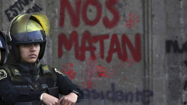 A woman police on the exterior of the National Palace during a demonstration against gender violence in Mexico City, Friday, Feb. 14, 2020