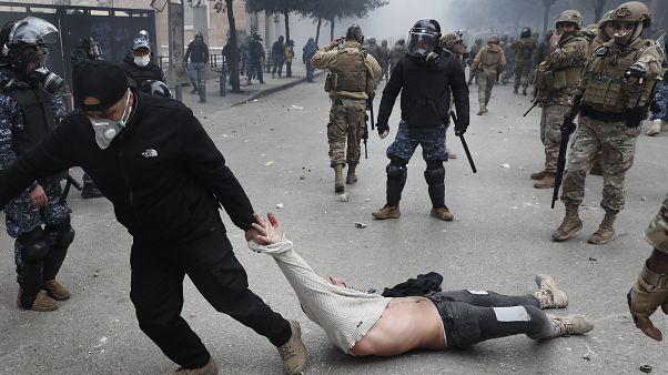 أحد عناصر الأمن البناني يجر متظاهرا في إحدى المظاهرات المناهضة للحكومة اللبنانية 11/02/2020
