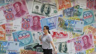 إمرأة تسيرة أمام مصرف للعملات في مركز الأعمال في هونغ كونغ بالصين. 06/08/2019