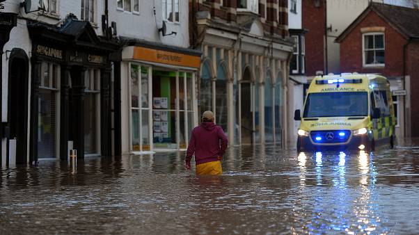 A man wades through flood water in Tenbury Wells, after the River Teme burst its banks in western England, on February 16, 2020.