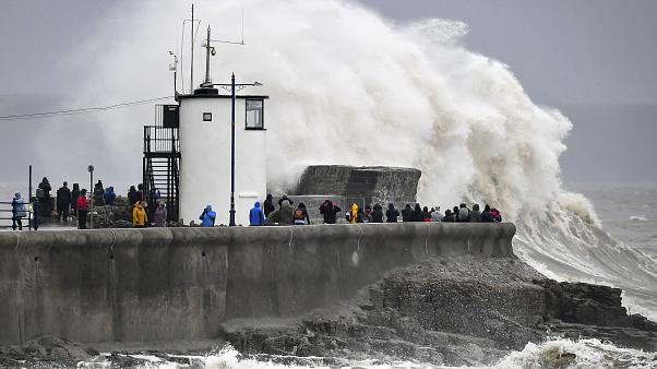 People watch waves and rough seas pound against the harbour wall at Porthcawl, Wales