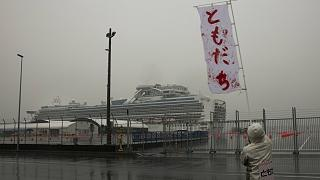 """رجل يلوح  بلافتة مكتوب عليها """"أصدقاء"""" باليابانية بالقرب من سفينة دايموند برنسيس"""