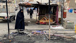 عراقية تتفقد بقايا الخيام وسط بغداد