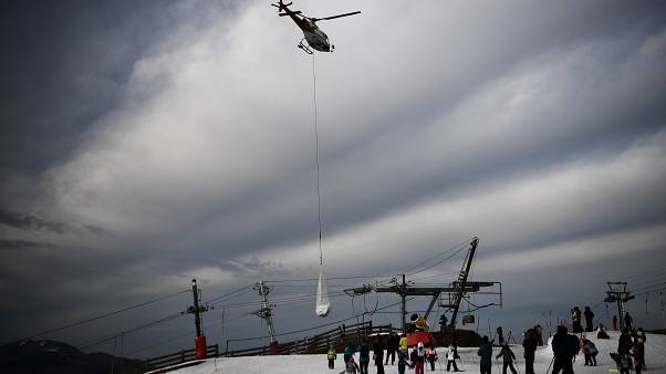 People look at an helicopter carrying snow in order to place it on a ski slope in the Superbagneres station in French Pyrenees mountain, on February 15, 2020.