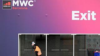 Un trabajador limpia las puertas de cristal en la sede del Congreso Mundial Móvil del CMM el 12 de febrero de 2020 en el centro Montjuic de Fira Barcelona en Barcelona.
