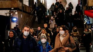 A family wearing a face mask walk in Biblioteka Imeni Lenina metro station in Moscow on February 7, 2020.
