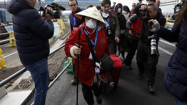 Passengers begin being taken off the quarantined Diamond Princess cruise ship Wednesday, Feb. 19, 2020, in Yokohama, near Tokyo. (AP Photo/Jae C. Hong)