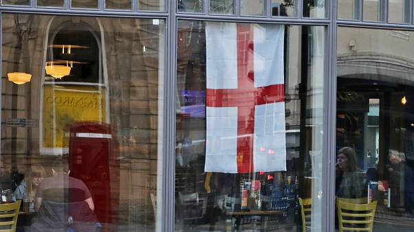 People sit in a pub, decorated with an English flag in Sunderland, England, March 13, 2019. (AP Photo/Frank Augstein)