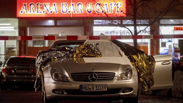 A car with dead bodies stands in front of a bar in Hanua, Germany Thursday, Feb. 20,