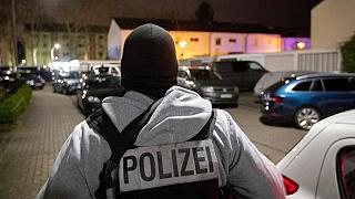 A police officer guards the road in front of a house that is searched through by police in Hanau, Germany Thursday, Feb. 20, 2020. (AP Photo/Michael Probst)