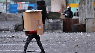 A protester covers his body while security force use slingshots to disperse anti-government protesters during clashes in downtown Baghdad, Iraq